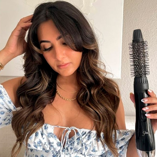 woman brush her hair with an electric brush