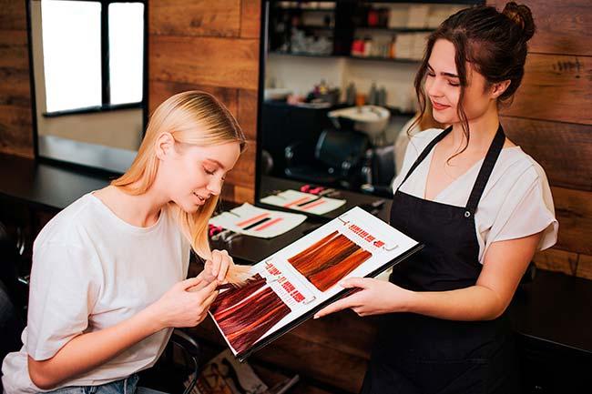 peluquera ayudando a clienta a elegir color de pelo